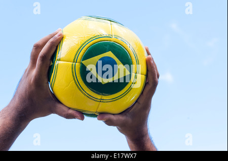 Man with throwing football with Brazil flag for Brazil World Cup 2014. - Stock Image