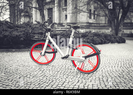 Bicycle with red wheels parked on sidewalk in the park. Black and white. Selective color effect - Stock Image