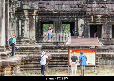 Angkor Wat, Cambodia - 11th January 2018: Chinese tourists posing for photos. They show liitle respect for ancient ruins. - Stock Image