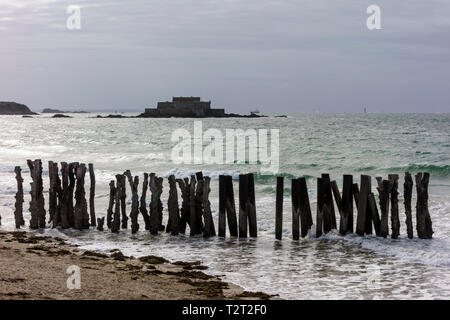 View of sea and groynes with Fort National in the background, Saint Malo, Brittany, France - Stock Image