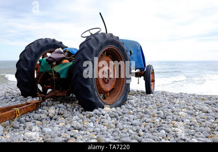 old rusty tractor on cromer beach, north norfolk, england - Stock Image