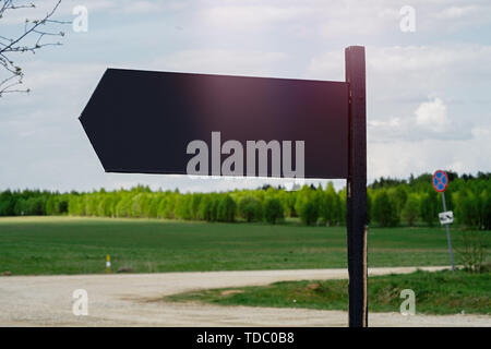 Close up of blank black outdoor road sign board at beautibul lanscape background. Copy space - Stock Image