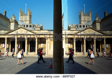 Historic Bath, UK -entrance to the King's and Queen's Baths, with the abbey tower visible behind. The right side of image is a reflection in a window. - Stock Image