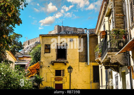 Broken hollowed out windows in an old building at the base of the Acropolis Hill as the Greek Flag flies on the historic Acropolis in Athens Greece - Stock Image