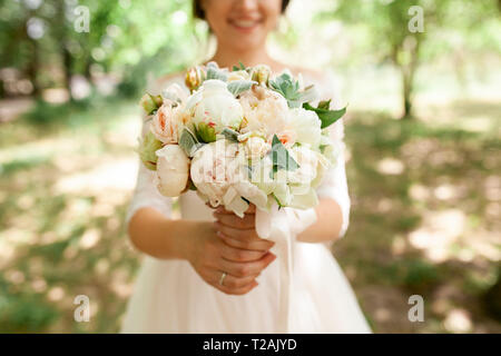 Bride holding bouquet of roses - Stock Image