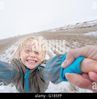 Parent swinging boy by the arm - Stock Image