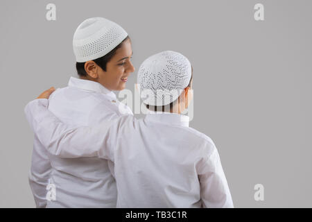 one young muslim boy holding other muslim boy by shoulder - Stock Image