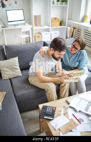 Young man trying to solve financial problems to pay monthly bills while his wife supporting him - Stock Image