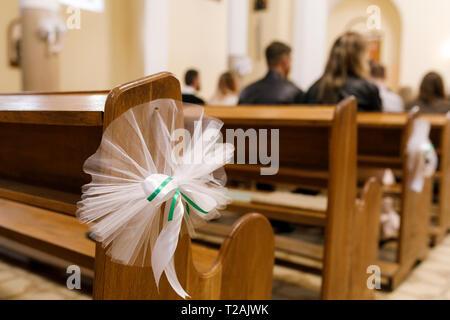 Tulle wedding decoration on pew - Stock Image