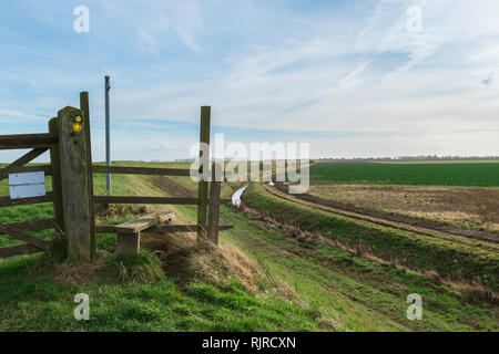Fen path stile, view of a footpath stile along the Sea Bank - an embankment separating arable fenland from The Wash, Lincolnshire, UK. - Stock Image