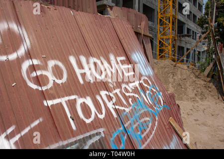 Spray painted sign making tourists feel unwelcome in Vang Vieng, Cambodia. - Stock Image