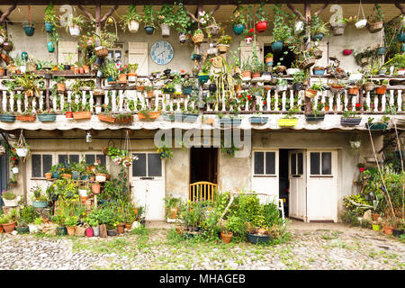 Facade of French house and balcony covered in flower pots and hanging baskets. - Stock Image