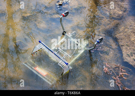 A shopping trolley for use with a wheelchair has been thown into the shallow water of the river Biss in Trowbrige and abandoned - Stock Image