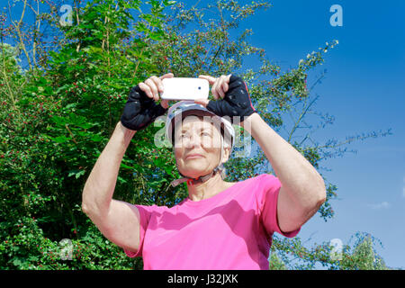 Senior woman in front of bushes and blue sky in summer sun with pink sport shirt, cycling gloves and helmet taking - Stock Image
