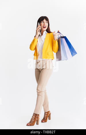 Image of a beautiful young business woman posing isolated over white background talking by mobile phone holding shopping bags. - Stock Image