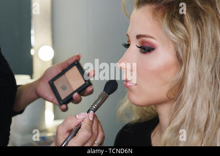 Make-up artist working in make-up studio, applying makeup on face of female clients. Makeup artist applies tonal powder. Evening make-up. - Stock Image
