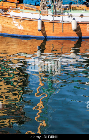 Reflection of an old sailing boat in the water at Nyhavn in Copenhagen, Denmark - Stock Image