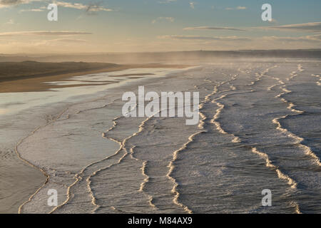 Breaking waves roll towards Saunton Sands at dawn in North Devon, England. Winter (January) 2018. - Stock Image