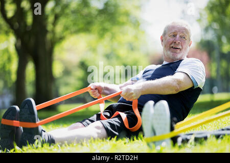 Active senior man exercising in park, stretching with resistance band - Stock Image