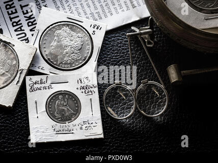Coin Collecting - Various Coins - Morgan Dollars - Seated Liberty - against backdrop of the Greysheet with magnifiers - Stock Image
