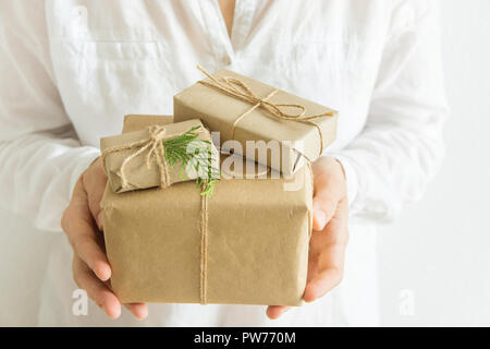 Young caucasian woman holds in hands gift box wrapped in craft paper tied with twine. White background pastel colors. Christmas New Years presents con - Stock Image
