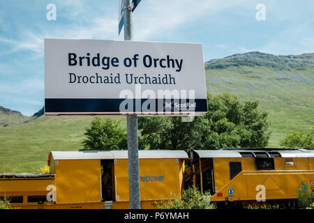 Station sign at Bridge of Orchy on the West Highland train line, with stoneblower machine in the background - Stock Image