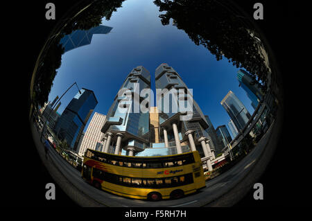 A yellow double decker bus in front of the Lippo center, Hong Kong SAR - Stock Image