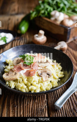 Delicious zucchini dumplings with roasted champignons, Prosciutto, grated, cheese and sour cream - Stock Image