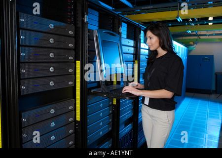 A young woman stands at a computer in a warehouse filled with servers. - Stock Image