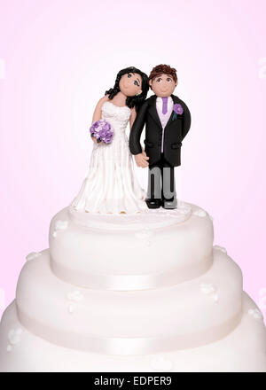 A cake topper showing the bride and groom - Stock Image