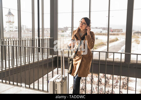 Businesswoman with baggage and cell phone applying earphones - Stock Image