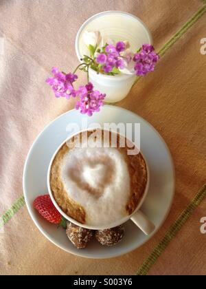 Cappuccino with sweets and flowers - Stock Image