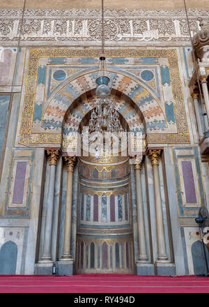 Colorful decorated marble wall with engraved Mihrab (niche) at the Mosque and Madrassa (School) of Sultan Hassan, Cairo, Egypt - Stock Image