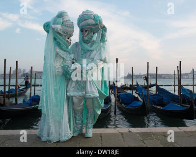 Venice, Italy. 25th Feb, 2014. A couple dressed in pale green elaborate costumes pose in front of gondolas at the waters edge. Venice Carnivale - Tuesday 25th February. Credit:  MeonStock/Alamy Live News - Stock Image