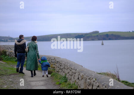 A family walking along a path in Cornwall, UK. - Stock Image