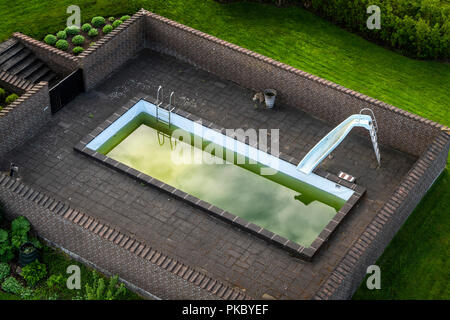 Terrace with a swimming pool with green water surrounded by a brick wall on a green lawn - Stock Image