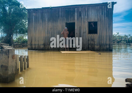 2015 flooding in Brazilian Amazon, normal daily life, man shaves in front of flooded house at Taquari district, Rio Branco city, Acre State. Floods have been affecting thousands of people in the state of Acre, northern Brazil, since 23 February 2015, when some of the state's rivers, in particular the Acre river, overflowed. Further heavy rainfall has forced river levels higher still, and on 03 March 2015 Brazil's federal government declared a state of emergency in Acre State, where current flood situation has been described as the worst in 132 years. - Stock Image