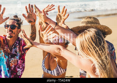 Friends people in summer vacation at the beach show their hands together dirt of sand after a funny day of activity at the sea lifestyle - group men a - Stock Image