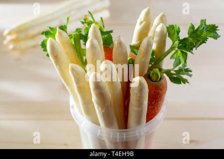 New harvest of white asparagus, high quality raw asparagus, carrot and selery in plastic bucket in spring season, ready to cook close up - Stock Image