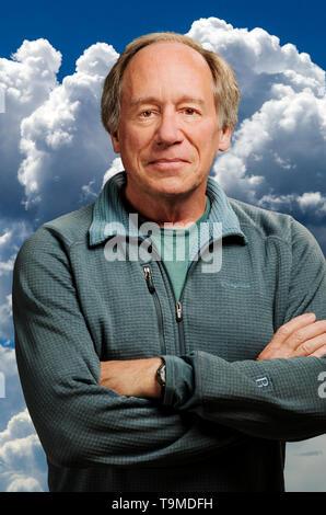 Portrait of confident middle aged man against cumulous cloud background - Stock Image