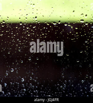 Fresh rain droplet on the surface of a glass window with unfocused background - Stock Image
