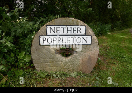 Nether Poppleton placename place name sign on stone wheel by the side of the road. - Stock Image