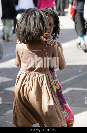 Two Little Girls Dancing Together at the Nottinghill Carnival 2010 - Stock Image