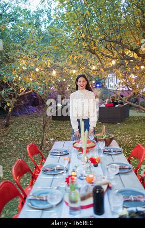 Portrait confident woman hosting dinner garden party - Stock Image