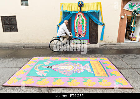 A Mexican man rides his bicycle around a floral carpet made from colored sawdust and decorated with flowers during the 8th Night Celebration marking the end of the Feast of St Michael in the central Mexican town of Uriangato, Guanajuato. Every year the town decorates 5km of road with religious icons in preparation for the statue of the patron saint to be paraded through the town. Uriangato became an international sensation after wowing Brussels with their floral carpet displayed at the Brussels Grand-Place during the Belgium Floral Carpet festival. - Stock Image