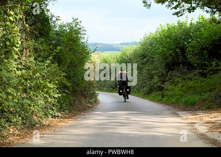 Rear back view of a male cyclist with panniers on his bike cycling in a lane in the rural Devon countryside in autumn England UK  KATHY DEWITT - Stock Image