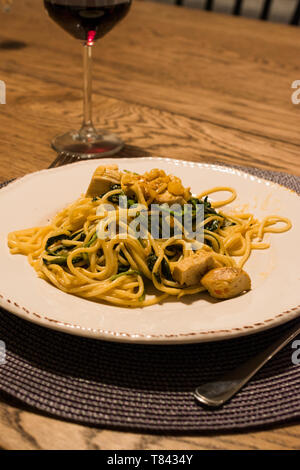 Homemade Spaghetti with Baby Spinach and Chicken at Dinner Table with Glass of Wine. Traditional Organic Food. - Stock Image