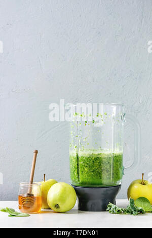 Green spinach kale apple honey smoothie in glass blender on white marble table with ingredients above. Healthy organic eating. - Stock Image