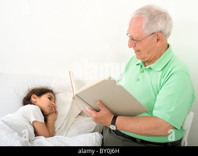 grandfather reading to grandchild a bed time story - Stock Image