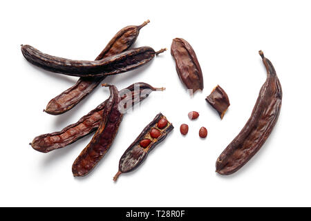 Carob bean pods and seeds on white background - Stock Image